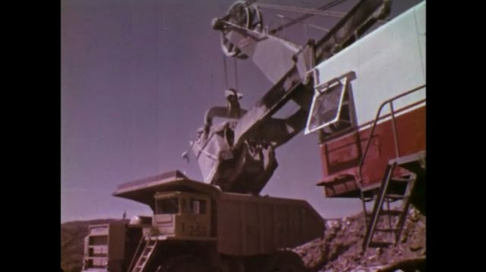 UNITED STATES: 1970S: machine loads rock into truck. Truck transports rock.