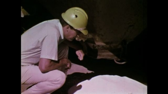 UNITED STATES: 1970S: man handles explosives by vehicle. Trucks drive to blast site. Construction work at canal site