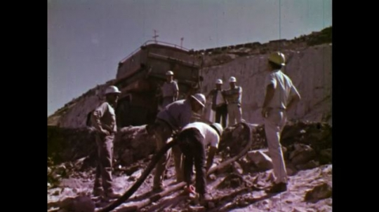 UNITED STATES: 1970S: men pump explosives into hole in ground. Ammonium nitrate mix added to blast site