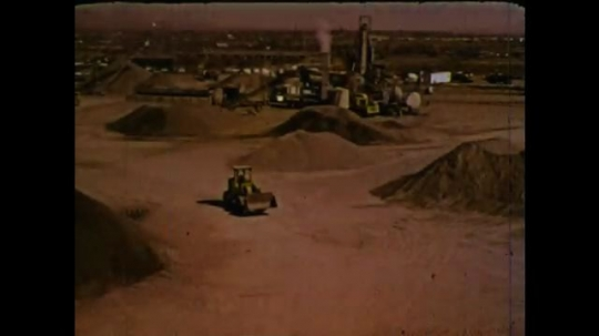 UNITED STATES 1970s: Piles of dirt. Front loader truck drives. Machine pours dirt into pile. Valley of dirt roads.