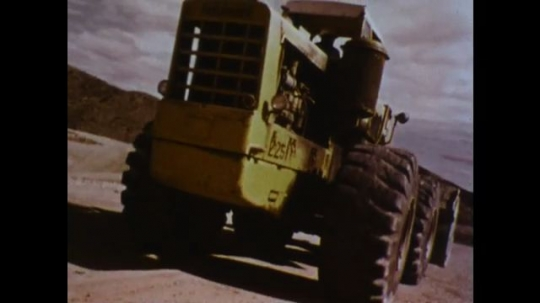 UNITED STATES 1970s: Front loader drives. Steering wheel of front loader. Front loader swerves side to side. Edge of cliff. Four men run out of way of front loader. Foot slams on brake.