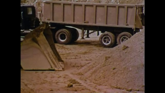 UNITED STATES 1970s: Front loader picks up dirt. Front loader backs up and dumps dirt in truck.