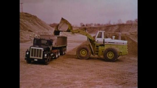 UNITED STATES 1970s: Front loader dumps dirt into truck. Truck drives. Man with hard hat and glasses.