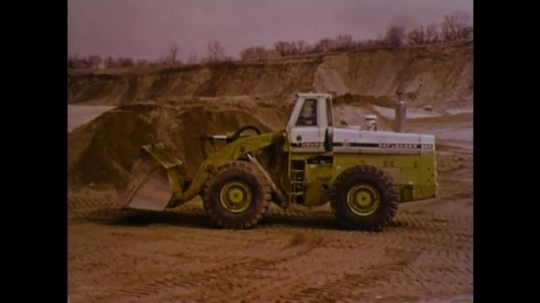 UNITED STATES 1970s: Front loader backs up. Front loader drives toward mountain of dirt. Man with hard hat and glasses.