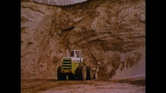 UNITED STATES 1970s: Front loader drives toward mountain of dirt. Dirt starts to fall. Front loader scoops up dirt from mountain and backs up.
