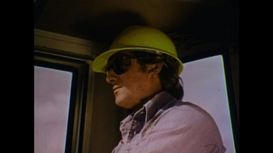 UNITED STATES 1970s: Man with hard hat and glasses. Front loader drives toward dirt. Front loader scoops up dirt. Dirt falls. Man looks up. Dirt falls. Man shields himself from falling dirt.
