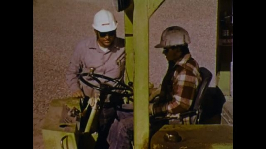 UNITED STATES 1970s: Driver uses controls. Men talk. Man climbs down from front loader. Driver turns on front loader.