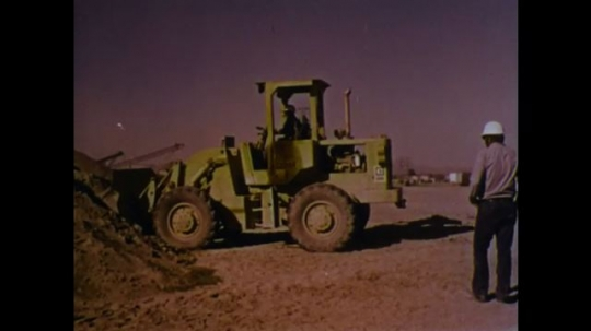 UNITED STATES 1970s: Front loader picks up dirt. Man watches. Man waves.