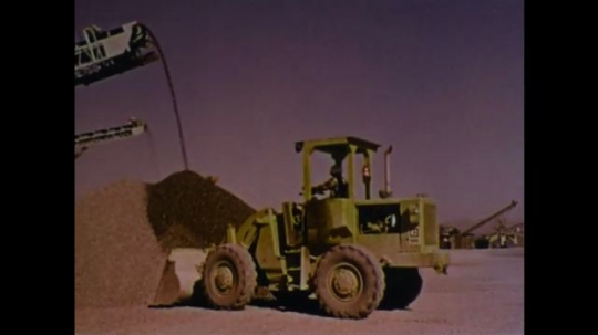 UNITED STATES 1970s: Front loader picks up dirt from pile as machine pours dirt into pile. Front loader backs up. Front loader drives with dirt.