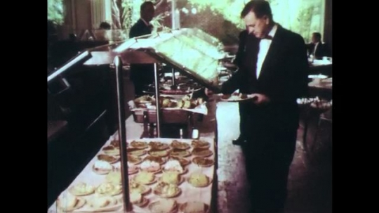 UNITED STATES: 1960s: Man takes food from buffet. Diners in restaurant.