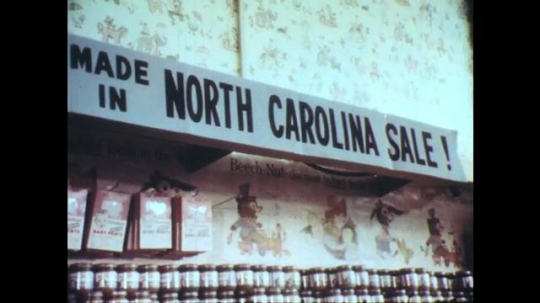 UNITED STATES: 1960s: North Carolina store sale. Fresh dressed poultry sign. Man interviewed by eggs.