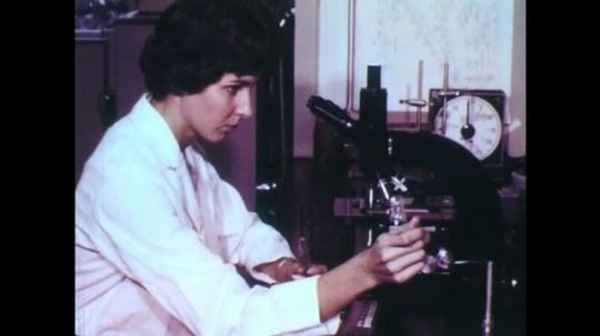UNITED STATES: 1960s: lady looks through microscope. Scientist researchers vegetables.