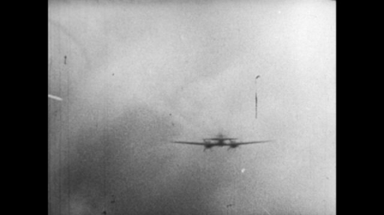 Europe 1940s: sparks of light from gunfire on plane. Planes fly through cloud during attack. Close up of plane in air. Wreckage of German plane in sea.