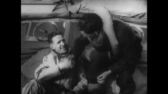 Europe 1940s: men shake hands after rescue. Wreck of plane on ground. Dead man on stretcher. German soldiers. Prisoners of war. Flames and fire after plane crash. Hitler talks to man.