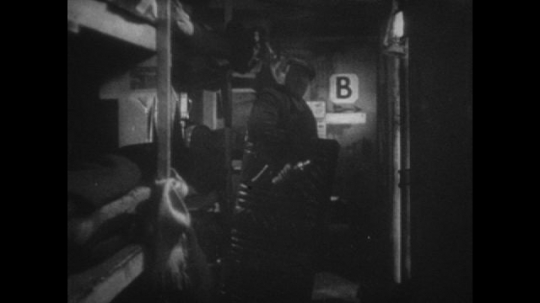 Europe 1940s: man talks to lady in air raid shelter. Vicar helps family with air raid shelter bunk bed. Man in shelter plays mouth organ.
