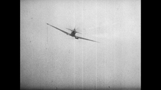 Europe 1940s: aircraft in sky during battle. Men operate anti aircraft gun. Plane in flames in air. Smoke trails from damaged plane in sky. Close up of gun and plane fire.