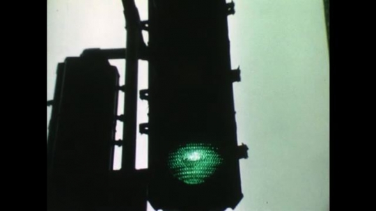 United States 1960s: close up of traffic light at green. Abstract green colour and pattern transition. Check out counter with green background. Three ladies in front of check outs.