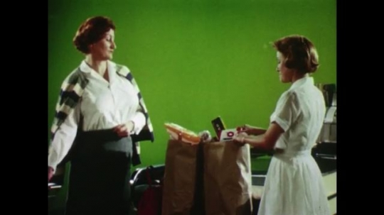 United States 1960s: lady looks at check out girl. Lady unfolds shopping trolley. Check out lady frowns. Ladies push trolleys towards till. Lady screams. Close up of lady
