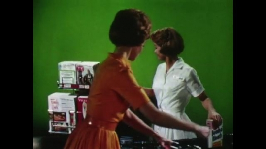 United States 1960s: Supermarket assistant tells customer the cost of groceries. Lady gives vouchers to worker. Customers bring shopping to tills.