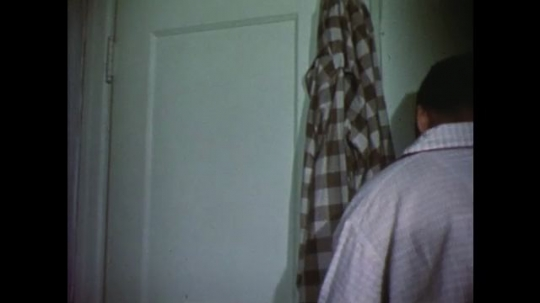 UNITED STATES: 1950s: Man stretches and opens door to bedroom cupboard. Man opens door and items fall on him. Ladies chat by door of house. Man shaves cream from face. Lady talks to man as he shaves.