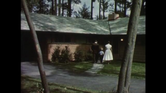UNITED STATES: 1950s: Family visit show home. Family drive car to show house.