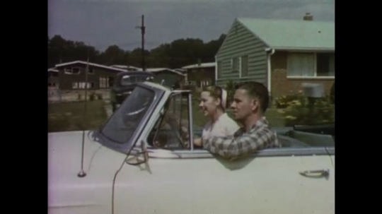 UNITED STATES: 1950s: Young couple laugh and smile as they travel through street in car. Couple visit show home.