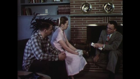 UNITED STATES: 1950s: Young couple talk to man in house. Man shows couple a television. Man points at list of property ownership benefits.