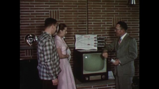 UNITED STATES: 1950s: Young couple talk to man in house. Man shows couple a television. Man points at list of property ownership benefits. Close up of brick house benefits.