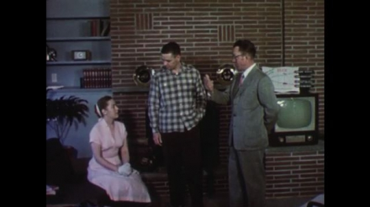 UNITED STATES: 1950s: Show house man talks to young couple. Man gives customers his card. Men shake hands in room. Couple leaves show home.