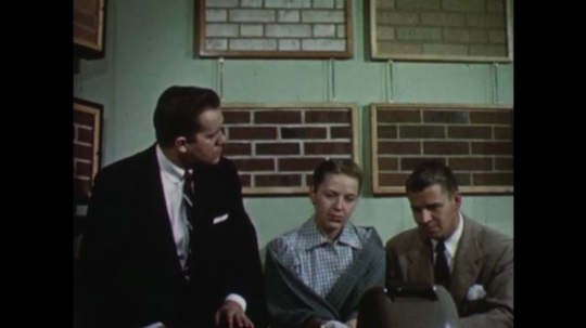 UNITED STATES: 1950s: Young couple talk to man. Man points at brick samples.