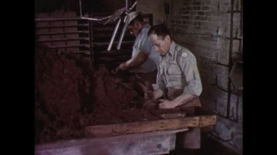 UNITED STATES: 1950s: Men pack brick clay material into moulds. Man scrapes clay in mould. Bricks in factory. Dried bricks on white background.