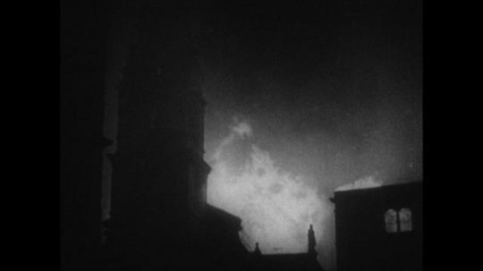 Europe 1940s: Tailors shop on fire at night. Buildings on fire at night. Firefighters spray water on fires.