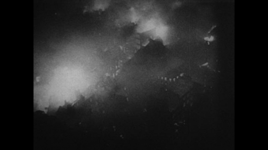 Europe: 1940s: London city buildings on fire, view from above. Men use searchlights to detect aircraft. Pilot in plane. Bullets fired from plane. Soldiers fire at enemy