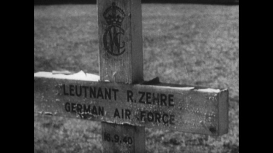 Europe: 1940s: grave marker for Lieutenant R.Zehre German Air Force. Crosses in field. Bus in street. Damaged buildings, Dead and wounded people.