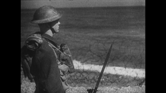 Europe: 1940s: soldier patrols beach. Soldier stands by guns. Hitler in war rooms. Nazi eagle sculpture. Men with rifles