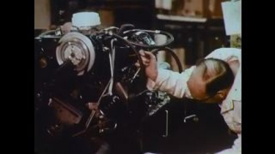 UNITED STATES: 1960s: man inspects engine. Engine fitted into body of car. Car production line. Workers fit out cars.