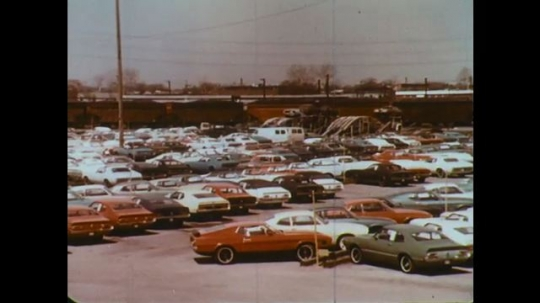 UNITED STATES: 1960s: Car drives around factory parking lot. Train line to factory.