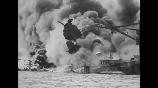 United States: 1940s: flames, clouds, and smoke around sinking ship in sea.