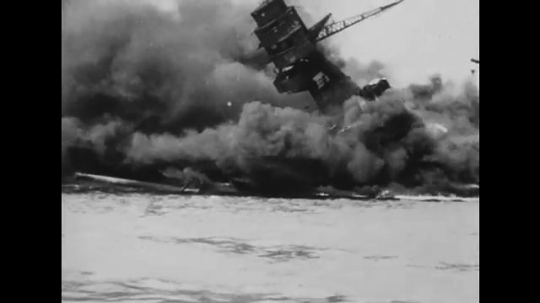 United States: 1940s: flames, clouds, and smoke around sinking ship in sea. Men in rescue boat. Guns on ship.
