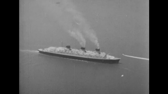 United States: 1940s: view of ship from above. Plane flies above ship. Smoke from chimneys on ship. Ship by city.