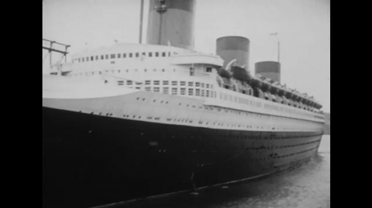 United States: 1940s: SS Normandie on mooring in harbor. Sailor in uniform on deck of ship.