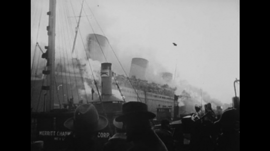 United States: 1940s: men on dock look at ship. Men on deck of ship. Cranes by ship. Smoke around ship. Men climb down ladder from ship. Men on stretchers.
