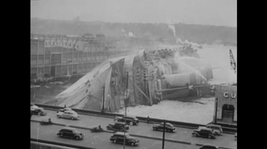 United States: 1940s: ship on side in dock. Cars drive past dock yard. Man films ship. Bottom of ship.