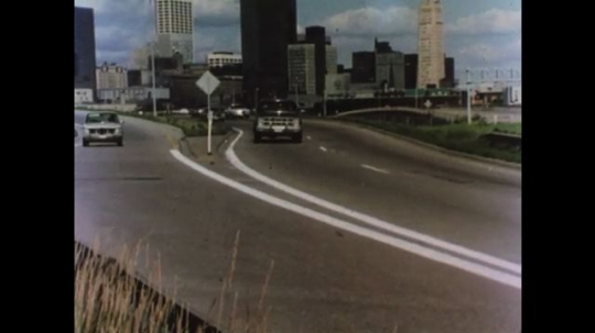 UNITED STATES 1970s: Cars drive on city highway. Car parallel parks.