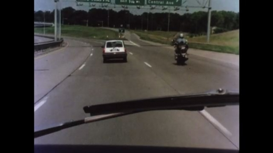 UNITED STATES 1970s: Car cuts in front of motorcycle to make exit off highway. Motorcyclist avoids car. Woman drives. Woman makes U-turn.
