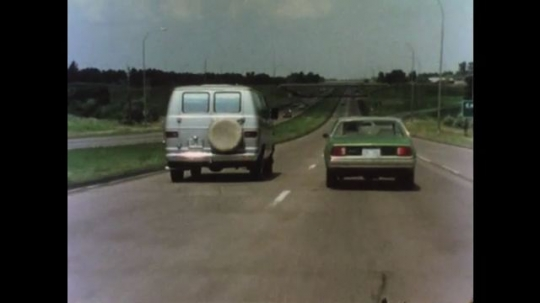 UNITED STATES 1970s: Car and van drive on highway side by side. Man checks passenger side mirror. Woman drives car.