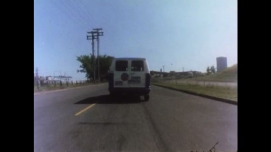UNITED STATES 1970s: Van drives on road. Car stops short. Steering wheel. Car is in rear view mirror. Car in mirror gets closer. Car in rear view mirror.