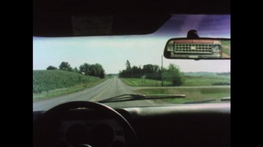 UNITED STATES 1970s: Car in rear view mirror. Car in rear view mirror goes out of view. Hand pulls over to avoid car. Car drives behind truck with windshield wipers  Alleyway.