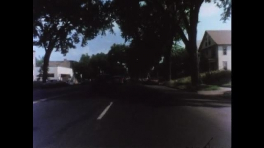 UNITED STATES 1970s: Car view drives in right lane. Passes cars in the left lane. Drives through green light.
