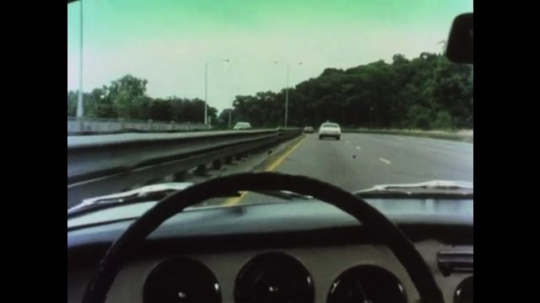 UNITED STATES 1970s: Steering wheel view drives in left lane on highway. Car in front brakes. Steering wheel view changes lanes. Guard wall. Guard wall with tire skids.